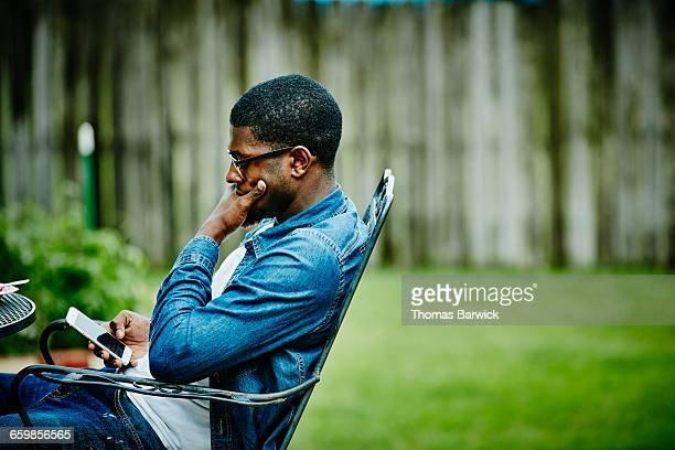 Man seated in backyard checking smartphone