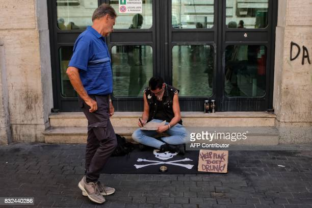 A man seated on a pirate flag begs for money with a cardboard reading 'Help punk to get drunk' on August 16 2017 in a street of Rome / AFP PHOTO /...