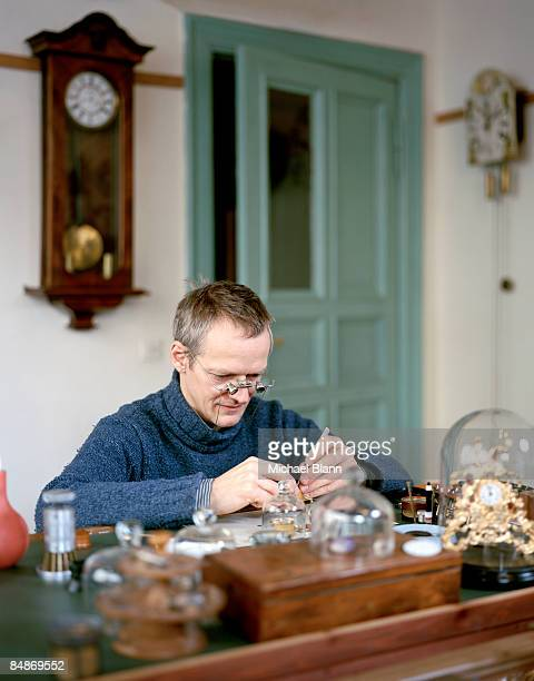 man seated repairing watches in shop