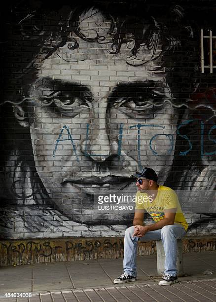 A man seats by a graffiti depicting Argentine musician Gustavo Cerati in Cali Colombia on September 4 2014 Cerati one of the greatest stars of the...