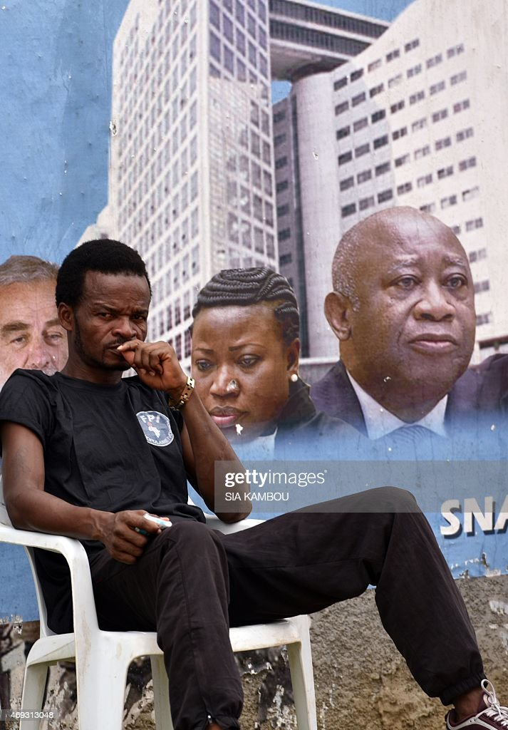 A man seats in front of a banner picturing Ivory Coast's former president Laurent Gbagboand reading in French 'Commemoration of the 11th April) during a demonstration on April 11, 2015 in Abidjan on the anniversary of Gbagbo's arrest by the International Criminal Court of The Hague, on charges of crimes against humanity after post-election violence in 2011.