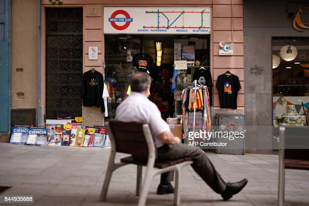 A man seats in front of a store selling tshirts depecting the Estelada the pro independence Catalan flag in Mataro on September 8 2017 Spain's top...