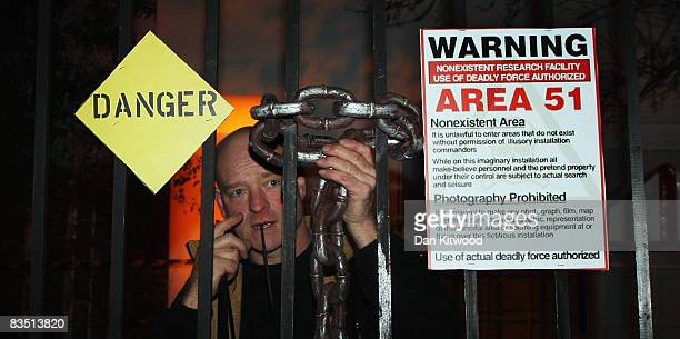 A man secures a chain on the gates as Jonathan Ross hosts a Halloween party at his home on October 31 2008 in London England An enquiry was held this...