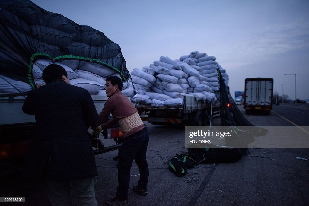A man secures cargo recovered from the Kaesong joint industrial area atop a truck on a roadside near a checkpoint of the Demilitarized Zone (DMZ) separating North and South Korea, in Paju on February 11, 2016. North Korea on February 11 expelled all South Koreans from the jointly-run Kaesong industrial zone and seized their factory assets, saying Seoul's earlier decision to shutter the complex had amounted to a 'declaration of war'. AFP PHOTO / Ed Jones / AFP / ED JONES
