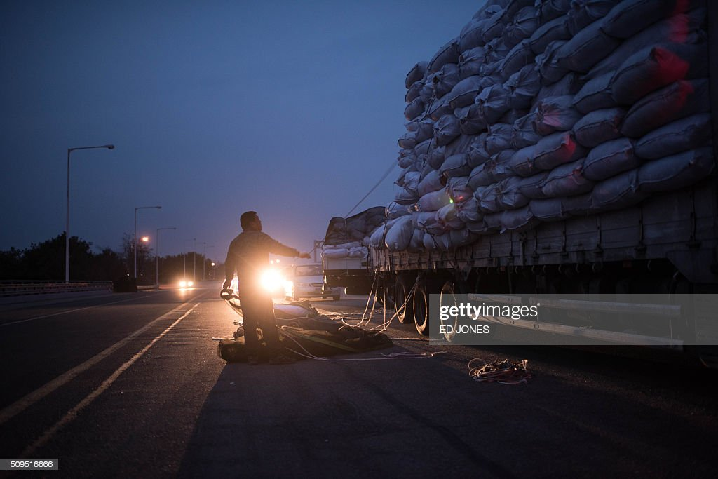 A man secures the cargo of a vehicle which arrived from the Kaesong joint industrial zone, on a roadside outside a checkpoint near the Demilitarized Zone (DMZ) separating the two Koreas in Paju on February 11, 2016. North Korea on February 11 expelled all South Koreans from the jointly-run Kaesong industrial zone and seized their factory assets, saying Seoul's earlier decision to shutter the complex had amounted to a 'declaration of war'. AFP PHOTO / Ed Jones / AFP / ED JONES