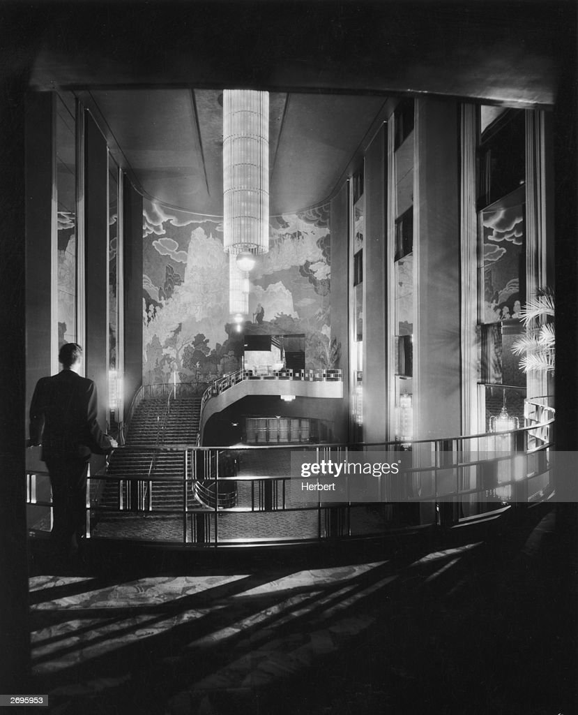 A man, seen from behind, leans against the railing of the gallery in the lobby of Radio City Music Hall in New York City. An Art Deco fresco decorates the opposite wall and a long chandelier lights the room.