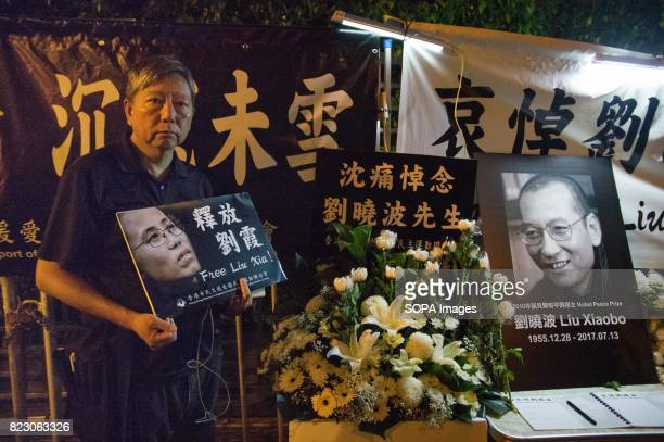 A man seen holding a plea card for Liu Xioabo Residents of Hong Kong hosted a vigil service outside the Chinese Liaison Office of Hong Kong after the...