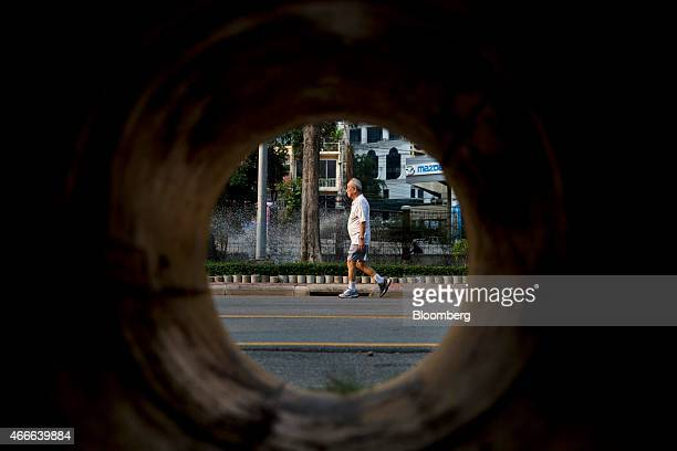 A man seen through a pipe walks in Lumphini Park in Bangkok Thailand on Sunday March 15 2015 Almost a third of Thailand's population will be over 60...