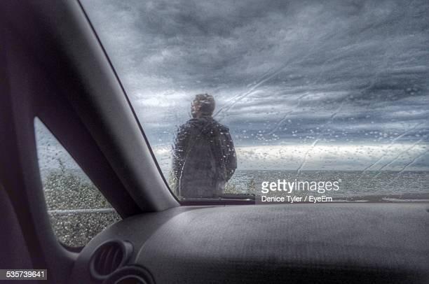 Man Seen Through Windshield Enjoying Rain