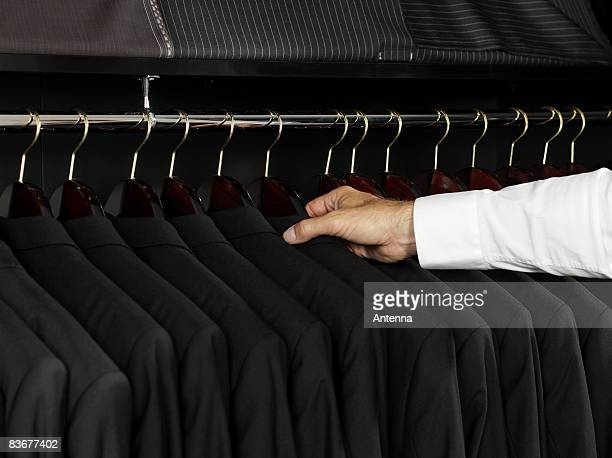 A man selecting a jacket from a clothing rack