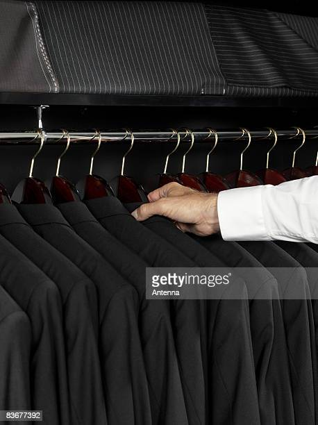 A man selecting a jacket from a clothing rail