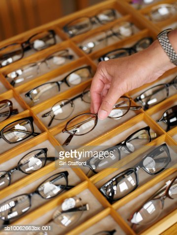 Man selecting a pair of eyeglasses from display case in shop, close-up of hand : Stock Photo