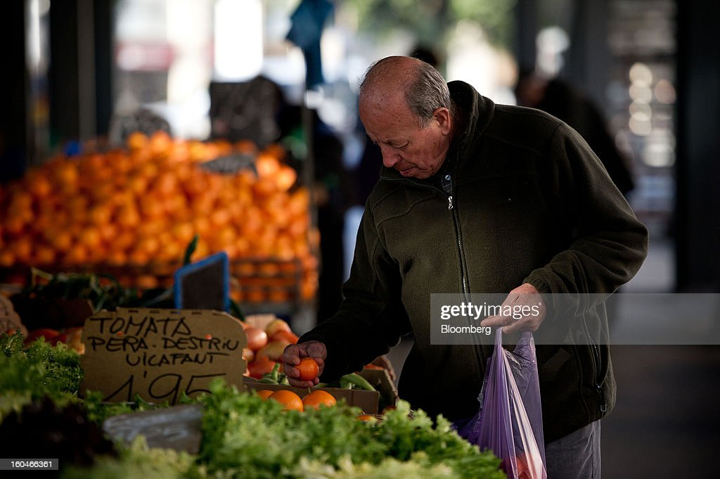 A man selects fresh tomatoes from a fruit and vegetable stall in the weekly market in Figueres, Spain, on Thursday, Jan. 31, 2013. Spain's recession deepened more than economists forecast in the fourth quarter as the government's struggle to rein in the euro region's second-largest budget deficit weighed on domestic demand. Photographer: David Ramos/Bloomberg via Getty Images