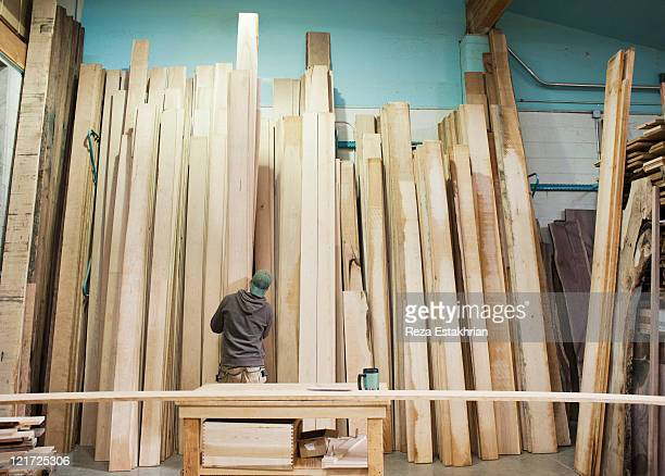 Man selects wood from racks