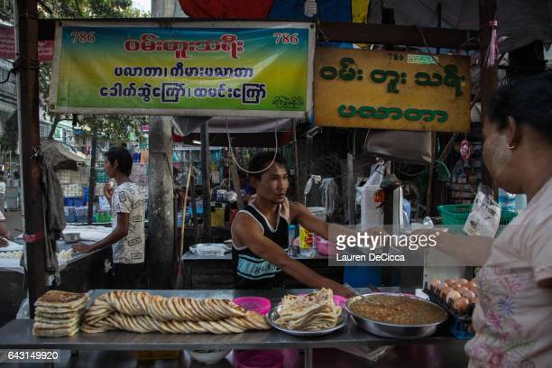 A man sell prata from a shop displaying a '786' sticker on February 20 2017 in Yangon Myanmar '786' is the numerical value associated with the...