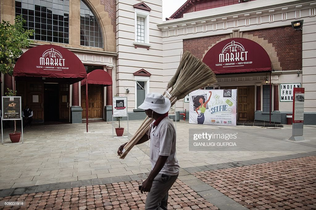 A man selling brooms walks by the main entrance of the Historic Market Theatre in Johannesburg on February 10, 2016. In 2016 the iconic Market Theatre marks its 40th anniversary, and as part of the celebrations some of its most socially relevant production will be revived to entertain and challenge a new audience. The Market Theatre was founded by theatre thespians Mannie Manim and Simon Barney, who were disturbed by the absence of a theatre that represented the voice of the majority or reflected what was happening in the skewed society of that era. / AFP / GIANLUIGI GUERCIA