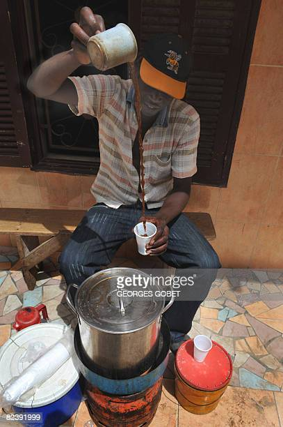 A man selling 'cafe touba' prepares a glass of coffee for a client on August 17 2008 on a street of Dakar where more and more residents can only...