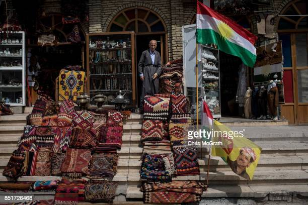 A man selling carpets is seen in front of his store decorated with political flags in the old city on September 22 2017 in Erbil Iraq The Kurdish...