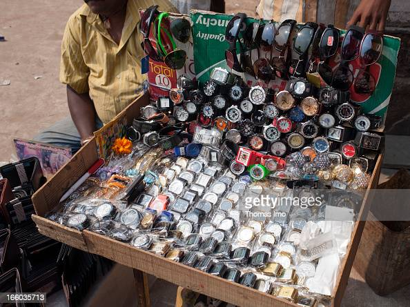Man selling fake watches imitations at a sales booth on the side of a road