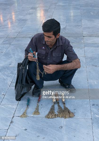 Man selling iron chains for children in Fatima alMasumeh shrine during Muharram Central County Qom Iran on October 8 2016 in Qom Iran