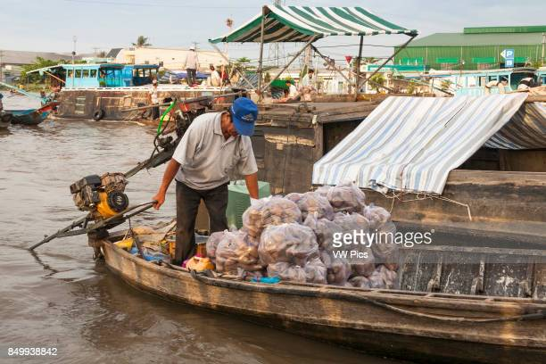 Man selling vegetables from a boat in the floating market Cai Rang near Can Tho Mekong River Delta Vietnam