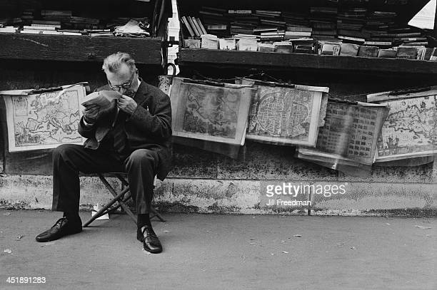 A man sells antique maps and second hand books at a street stall in Paris 1969