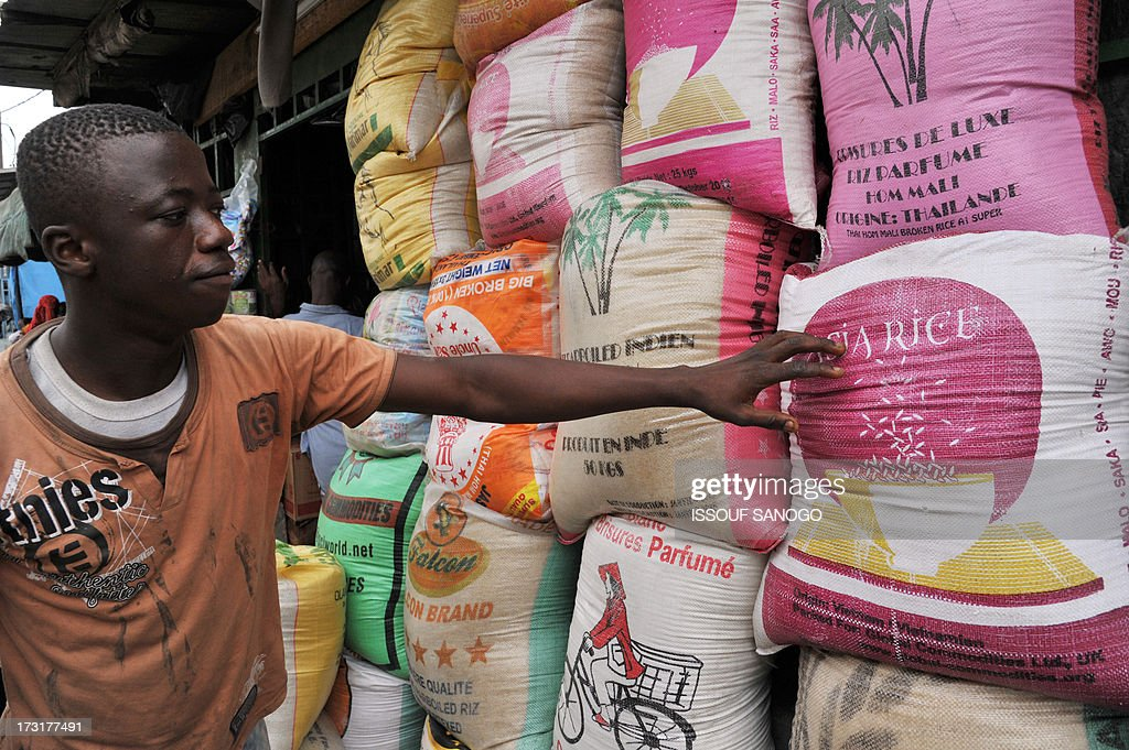 A man sells bags of rice in the market of Abobo, a suburb of Abidjan on July 9, 2013 in preparation for the Muslim holy month of Ramadan. The holy month of Ramadan, during which Muslims fast from dawn to dusk, begins with the sighting of the new moon, which varies from country to country.