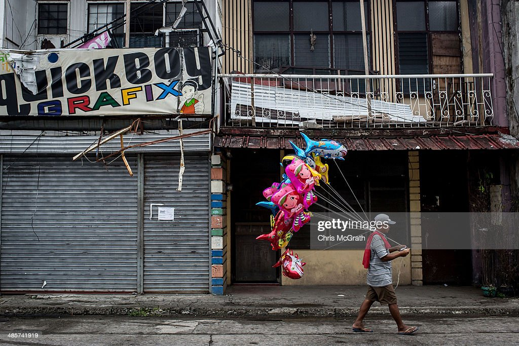 A man sells balloons on a street on April 20, 2014 in Tacloban, Leyte, Philippines. People continue to rebuild their lives five months after Typhoon Haiyan struck the coast on November 8, 2013, leaving more than 6000 dead and many more homeless. Although many businesses and services are functioning, electricity and housing continue to be the main issues, with many residents still living in temporary housing conditions due to 'No Build' areas preventing them from rebuilding their homes. This week marks Holy Week across the Philippines and will see many people attending religious activities.