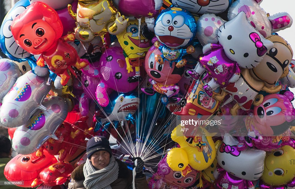 A man sells balloons on the banks of the Yalu River in the Chinese border town of Dandong opposite to the North Korean town of Sinuiju on February 10, 2016. North Korea has restarted a plutonium reactor that could fuel a nuclear bomb and is seeking missile technology that could threaten the United States, Washington's top spy said. AFP PHOTO / JOHANNES EISELE / AFP / JOHANNES EISELE