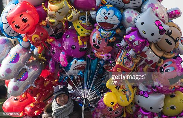 TOPSHOT A man sells balloons on the banks of the Yalu River in the Chinese border town of Dandong opposite to the North Korean town of Sinuiju on...