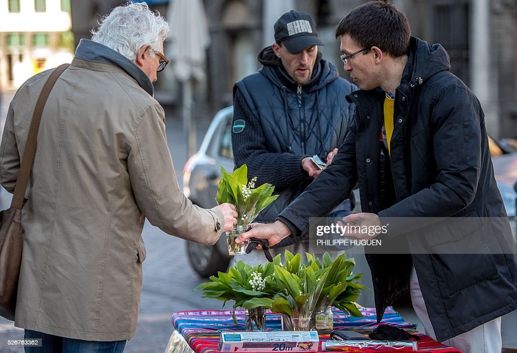 A man sells bouquets of lily of the valley flowers in Lille on May 1, 2016. / AFP / PHILIPPE