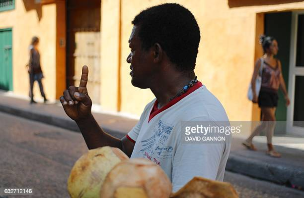 A man sells coconuts on the street in Cartagena Colombia on January 25 2017 / AFP / David GANNON