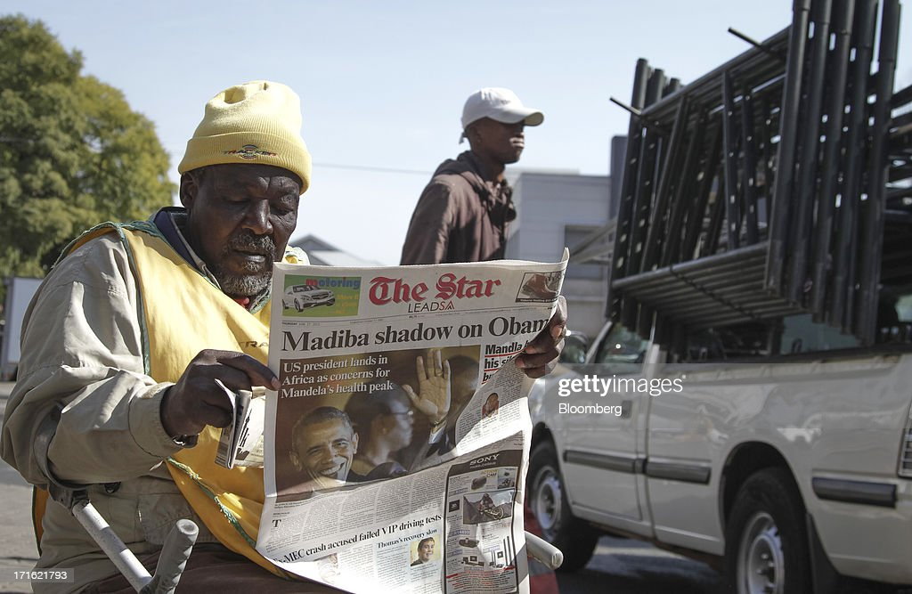 A man sells copies of The Star, a South African newspaper, while sitting by the by the roadside as the paper reports on the visit of U.S. President Barack Obama and the health of former South African president Nelson Mandela in Johannesburg, South Africa, on Thursday, June 27, 2013. South African President Jacob Zuma cancelled a trip to neighbouring Mozambique today after visiting Nelson Mandela, who remains critically ill in the hospital. Photographer: Nadine Hutton/Bloomberg via Getty Images