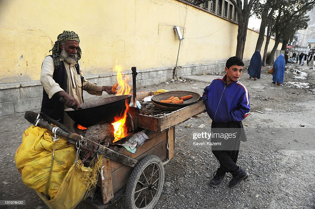 A man sells corns prepared in a pan on fire on the street on October 15, 2011 in Kabul, Afghanistan.