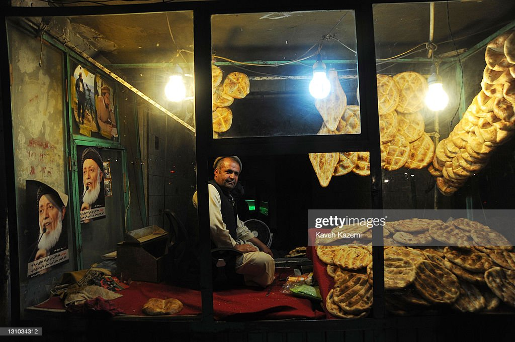 A man sells freshly baked bread displayed in the window where a picture of the recently assasinated ex Afghan president Borhaneddin Rabbani and Mujahedin commander Ahmad Shah Masoud are posted on the wall in Shahr-e Now neighborhood on October 16, 2011 in Kabul, Afghanistan.