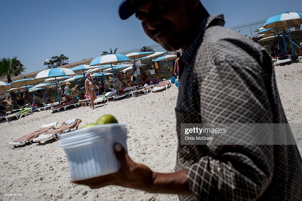 A man sells fruit along the waters edge as tourists enjoy the beach on June 25, 2016 in Sousse, Tunisia. Before the 2011 revolution, tourism in Tunisia accounted for approximately 7% of the countries GDP. The two 2015 terrorist attacks at the Bardo Museum and Sousse Beach saw tourism numbers plummet even further forcing hotels to close and many tourism and hospitality workers to lose their jobs. The 26th of June marks the first anniversary of the Sousse beach attacks.