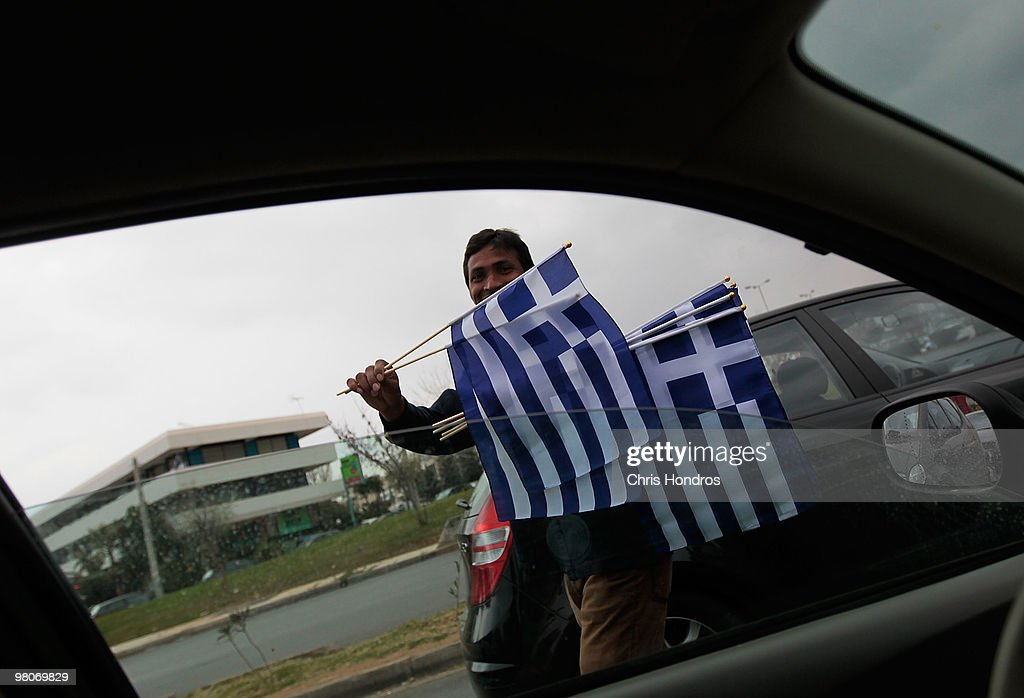 A man sells Greek flags to drivers passing by March 26, 2010 in Athens, Greece. Leaders of the sixteen euro zone countries along with the International Monetary Fund agreed March 26 to provide Greece with a 22 billion euro loan to help the country with its staggering debts, though it will only be available if open market lending to Greece dries up.
