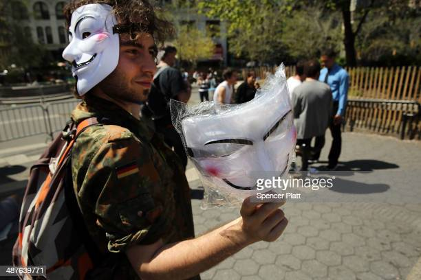 A man sells Guy Fawkes masks as demonstrators gather and prepare to march down Broadway on International Workers Day or Labor Day on May 1 2014 in...