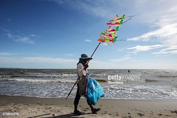A man sells kites while walking along Bang Saen beach near Pattaya Chonburi province Thailand on Thursday May 29 2015 The Thai economy may grow 35...
