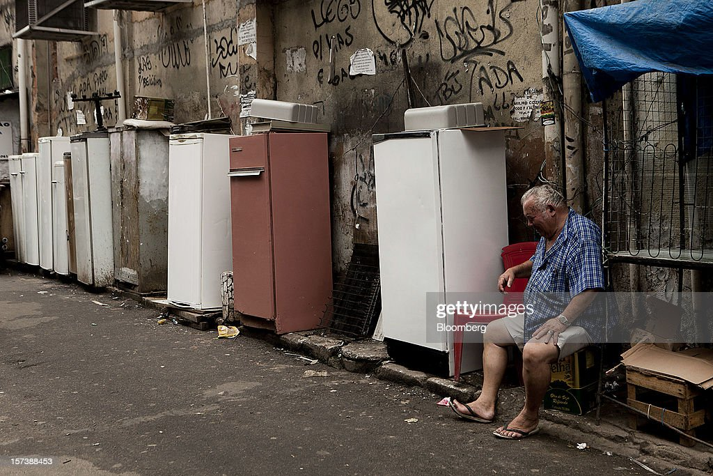 A man sells old refrigerators in the streets of the Rocinha slum in Rio de Janeiro, Brazil, on Wednesday, Nov. 28, 2012. About 56 percent of the 12 million people who live in slums like Rocinha were considered middle class in 2011, up from 29 percent in 2001, according to a study this year by Instituto Data Popular, a Sao Paulo-based research group. Photographer: Dado Galdieri/Bloomberg via Getty Images