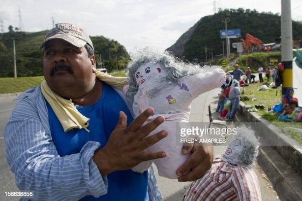 A man sells 'Old Year' dolls on the outskirts of Medellin Colombia on December 31 2012 It is a popular tradition in Colombia to burn 'Old Year' dolls...