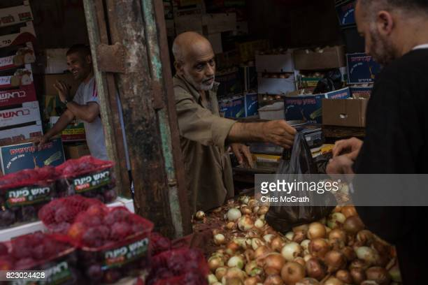 A man sells onions at a market on July 21 2017 in Gaza City Gaza For the past ten years Gaza residents have lived with constant power shortages in...