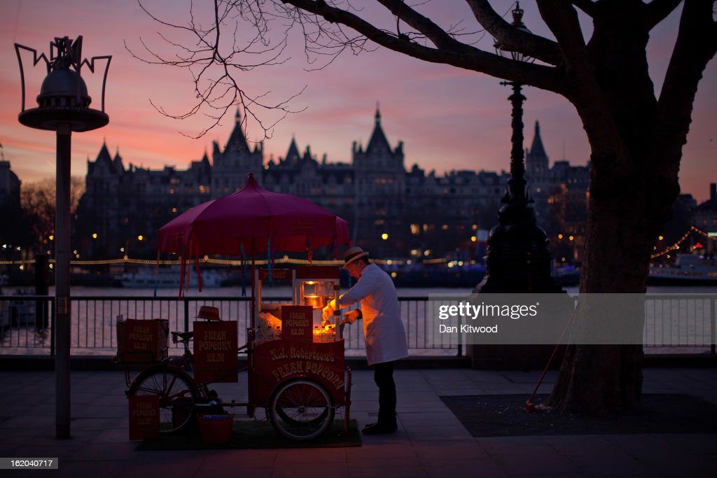 A man sells popcorn from a traditional cart at sunset on London's Southbank on February 18, 2013 in London, England.