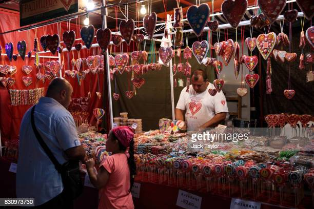 A man sells sweets and heartshaped treats from a stall in town during the Guca Trumpet Festival on August 10 2017 in Guca Serbia Thousands of...