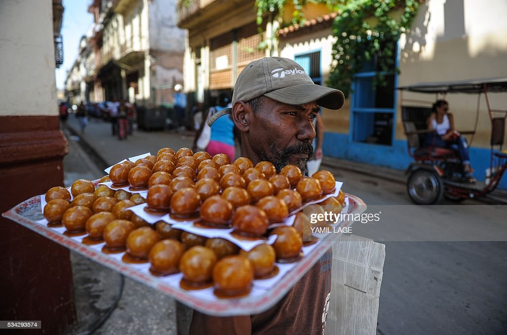 A man sells toffee coconuts in a street of Havana, on May 25, 2016. Cuban authorities are considering legalizing certain private businesses, a potentially transformative move for the communist island as it liberalizes its economy, according to proposals published this week. / AFP / YAMIL