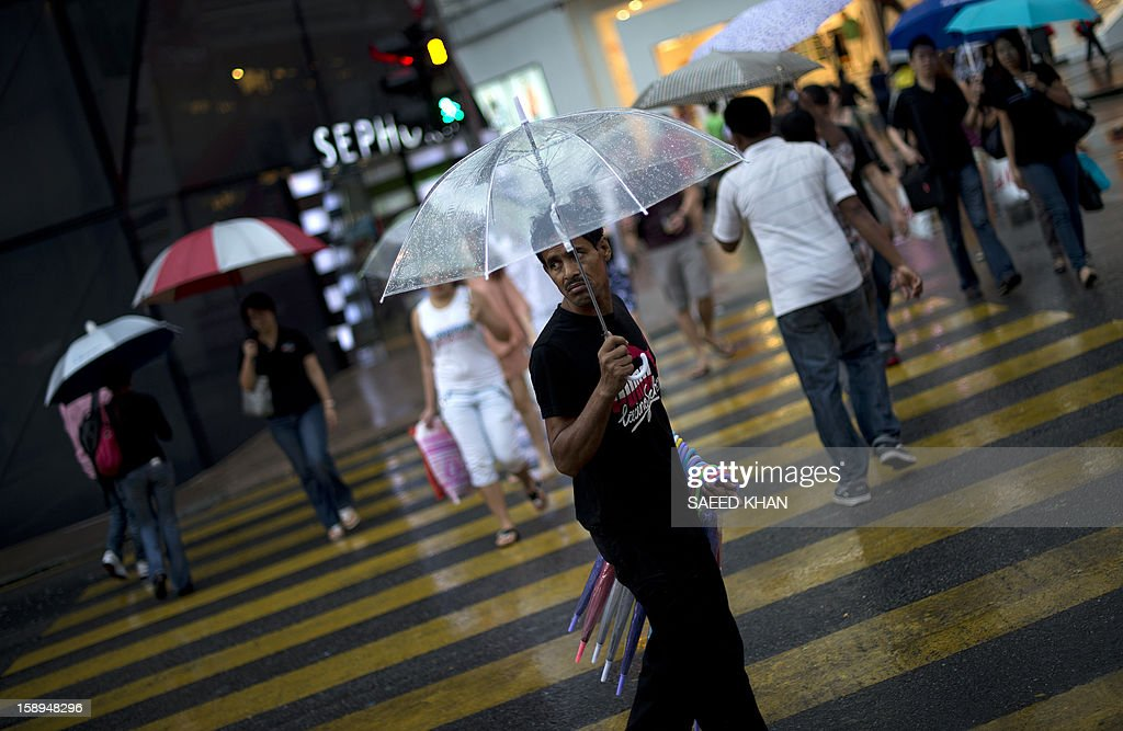A man sells umbrellas during a light rain outside a shopping mall in Kuala Lumpur on January 4, 2013. Malaysia is heavily reliant on migrant workers: they number about 2.2 million people and are the mainstays of the plantation and manufacturing sectors. AFP PHOTO / Saeed Khan