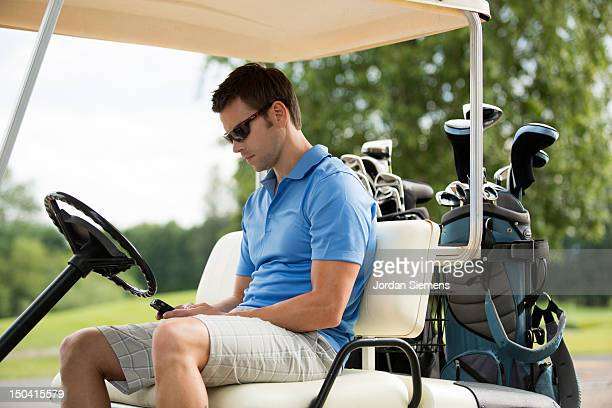 Man sending a text while golfing.