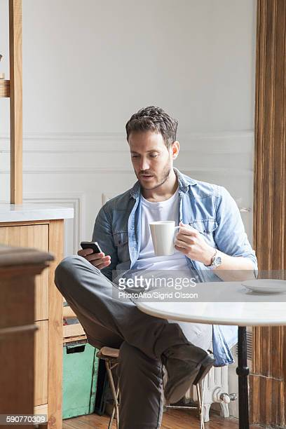 Man sending text message during coffee break