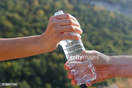 Man sends woman water bottle on camping trip in forest : Stock Photo