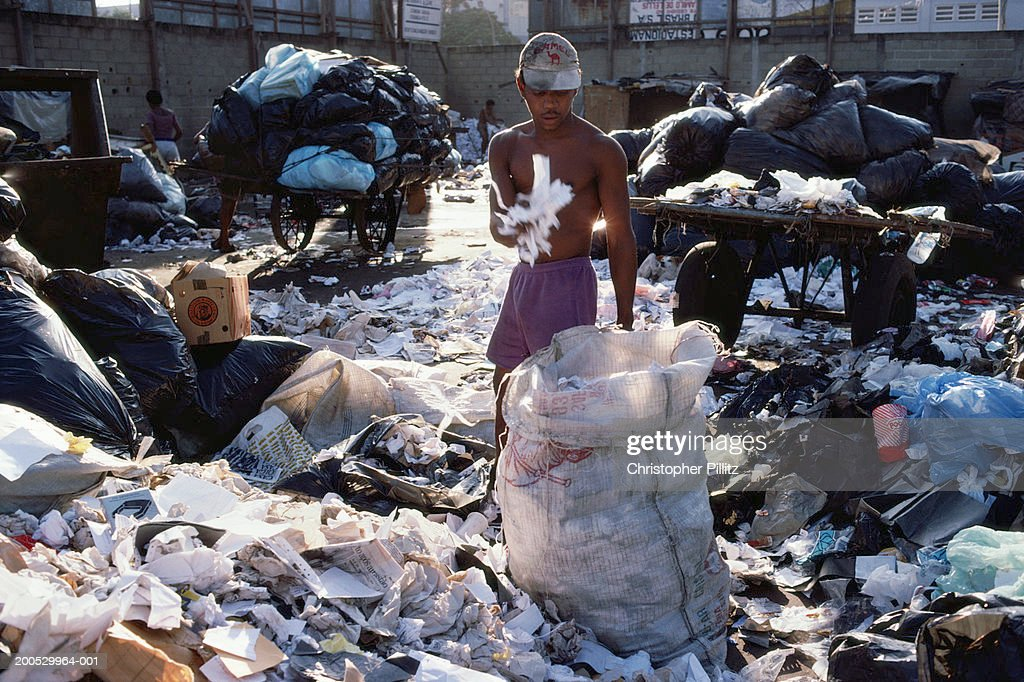 Man seperates paper and other material in recycling centre in Rio de Janeiro, Brazil. : Stock Photo
